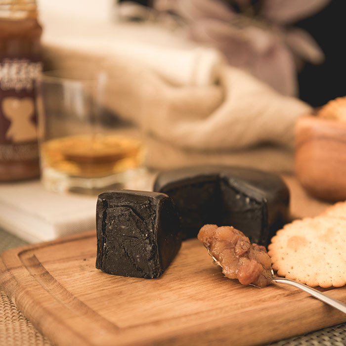Black truckle of cheese on wooden cheeseboard, cut open to show the black charcoal cheese. In the foreground there is a full spoon of chutney sat next to the truckle. There is the jar of chut