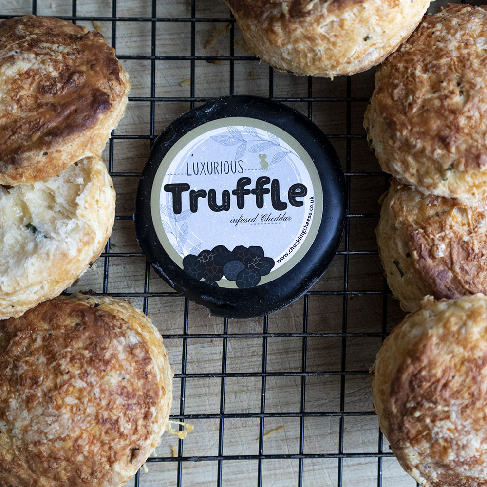 Golden cheese scones spread across a wire cooling tray. In the centre is the Truffle Cheese wax truckle packaging. One cheese scone on the left has been opened, showing the heavy flecks of tr