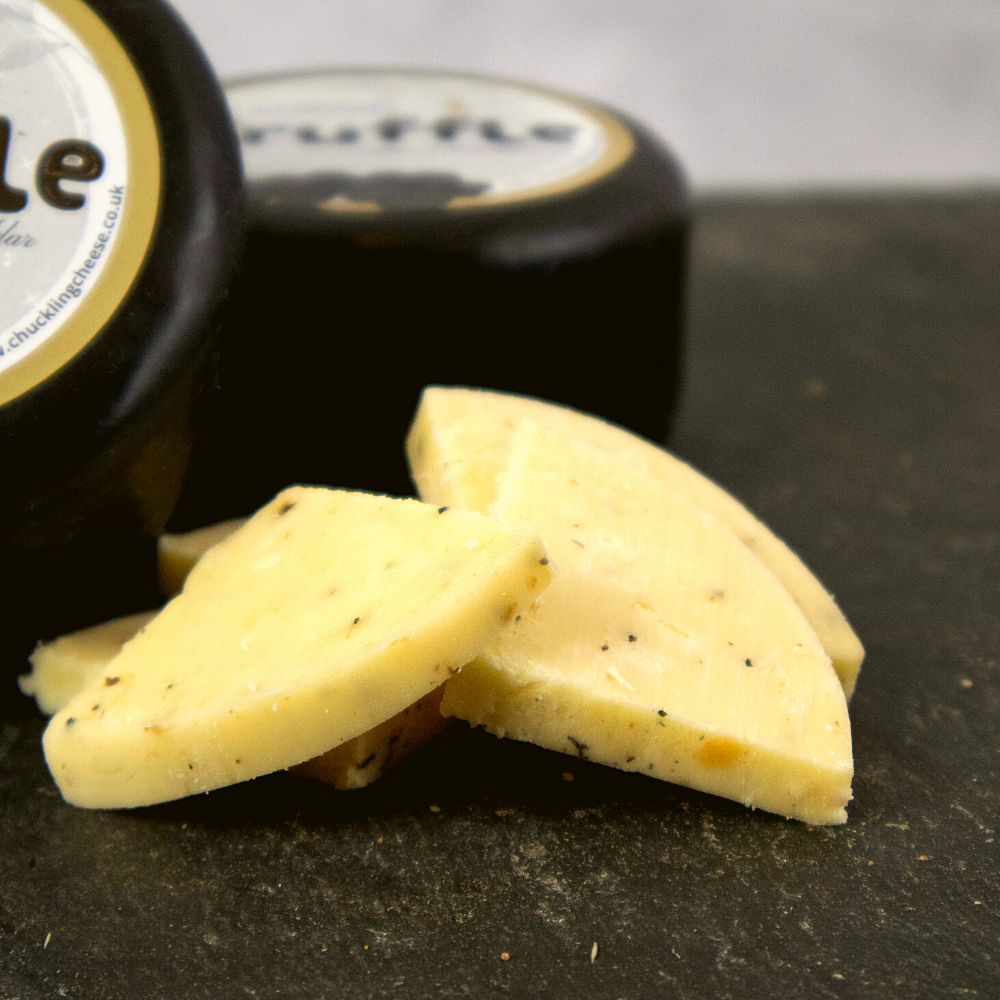 Close up of Luxurious Truffle Cheddar Cheese sliced into triangles with the black wax wrapped laid behind