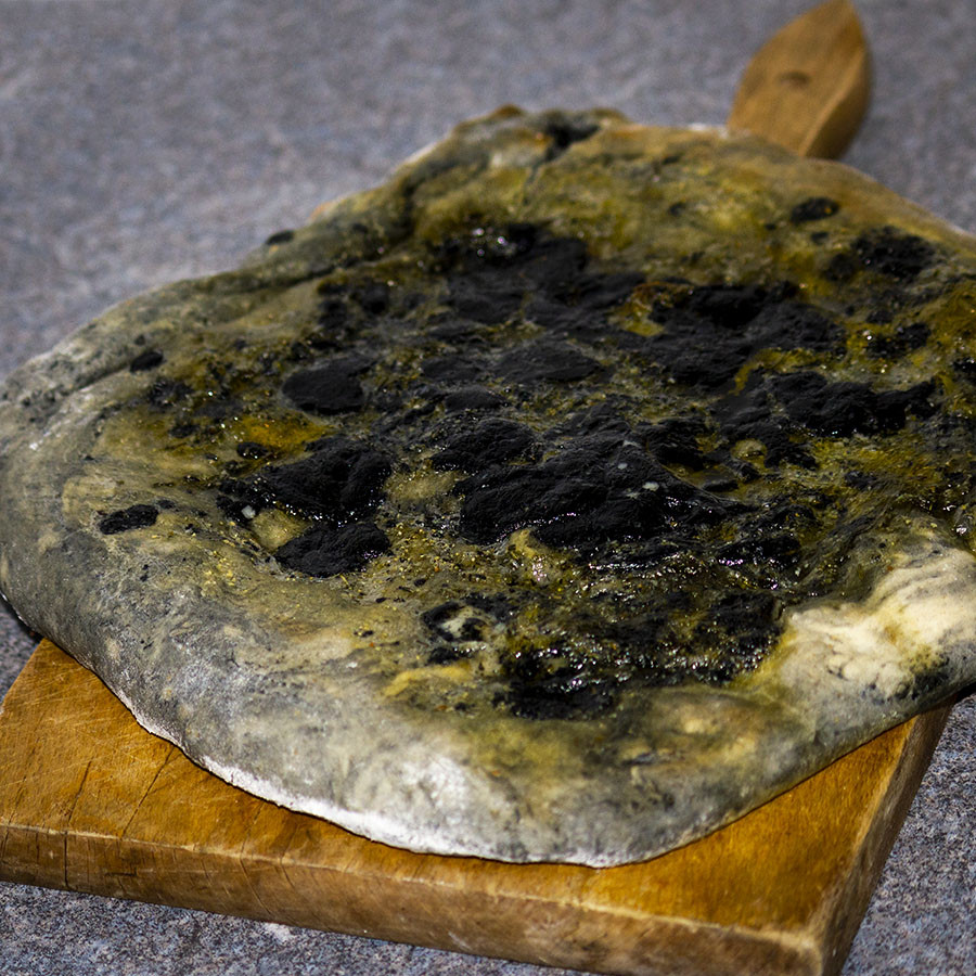 Freshly baked garlic pizza with melted Black as Coal Charcoal Cheddar Cheese