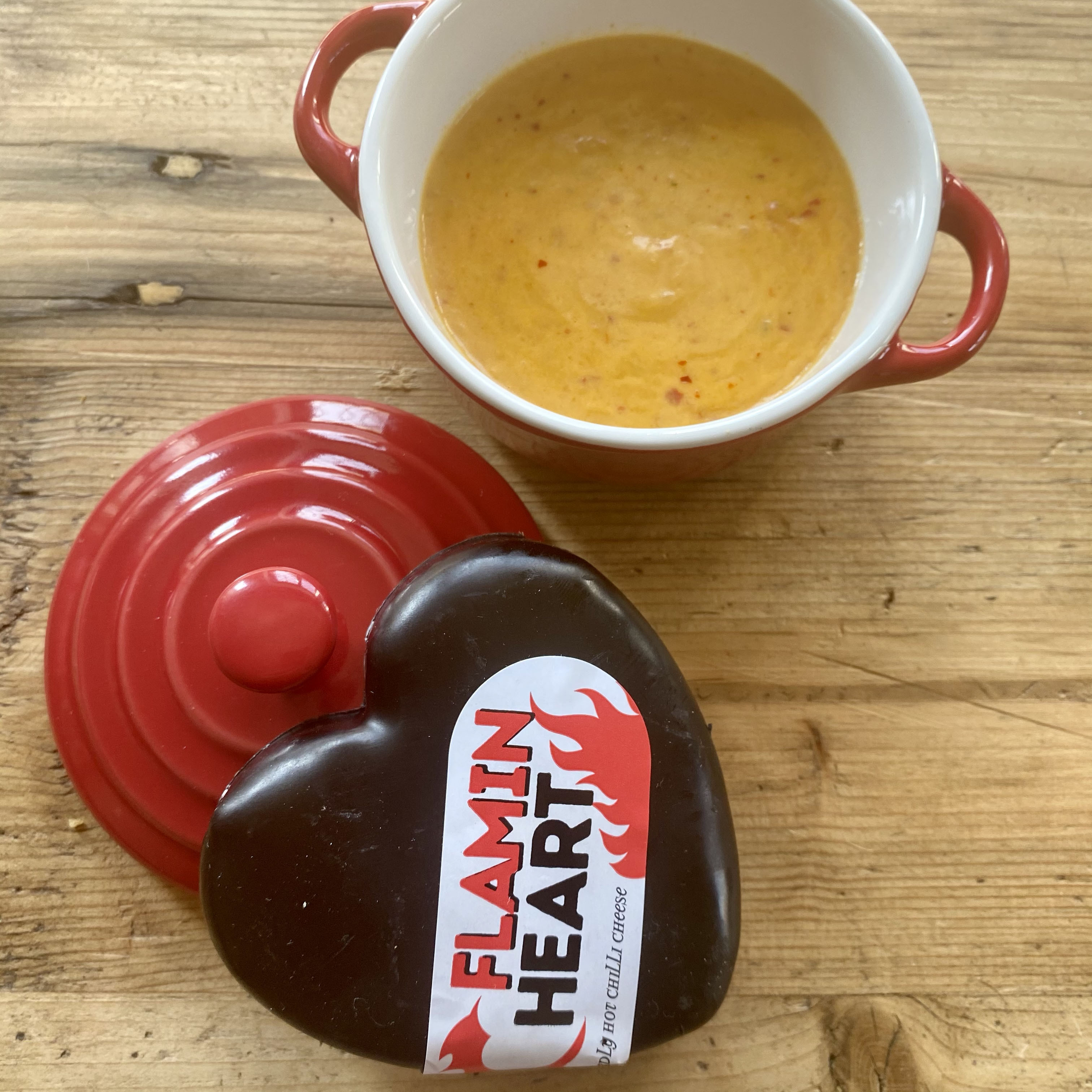 Red ramakin with bright orange chilli cheese dip with the black heart shaped chilli cheese truckle stood upon the ramakin lid.