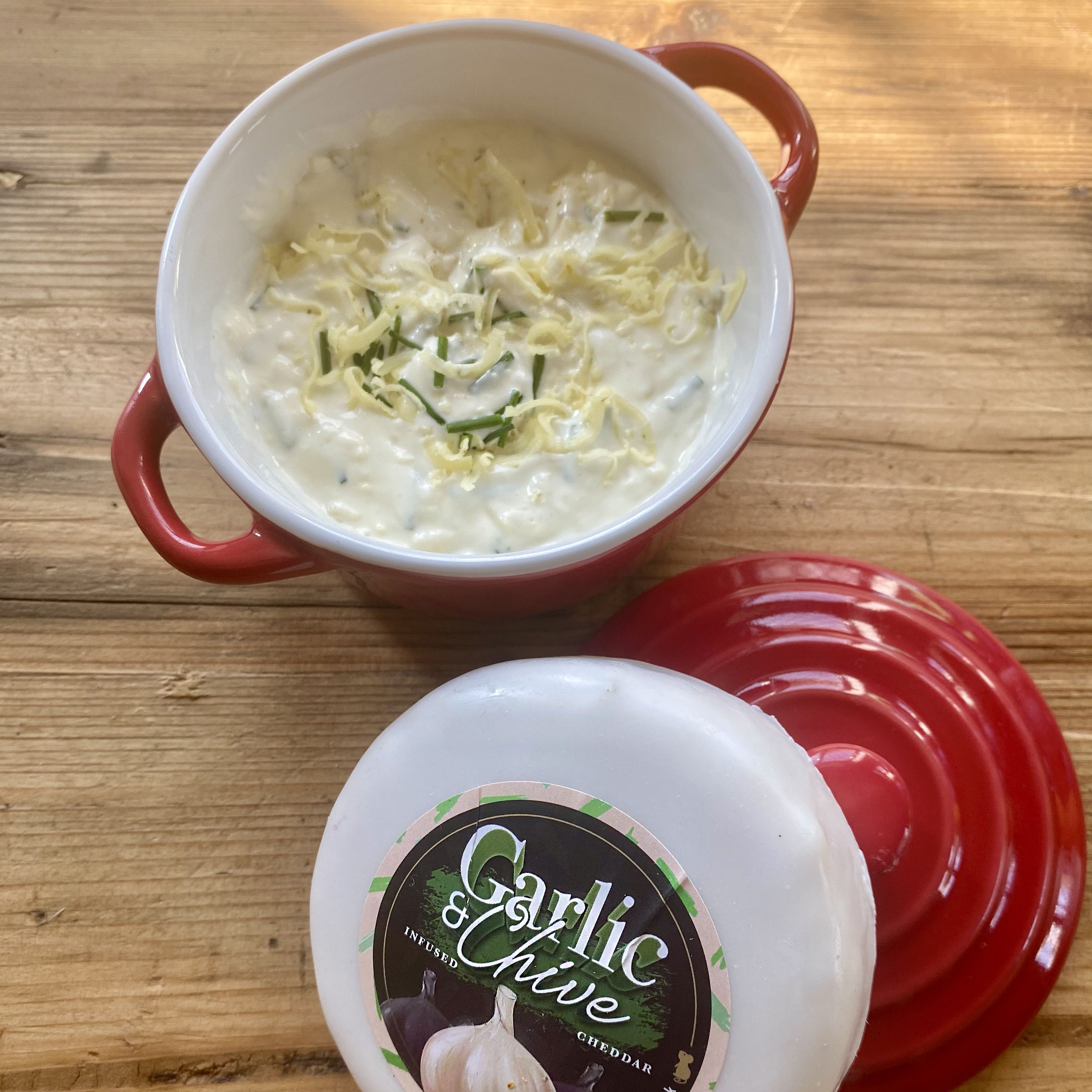Red ramakin with creamy, chunky garlic and chive cheese dip with the white Garlic and Chive cheese truckle stood upon the ramakin lid.