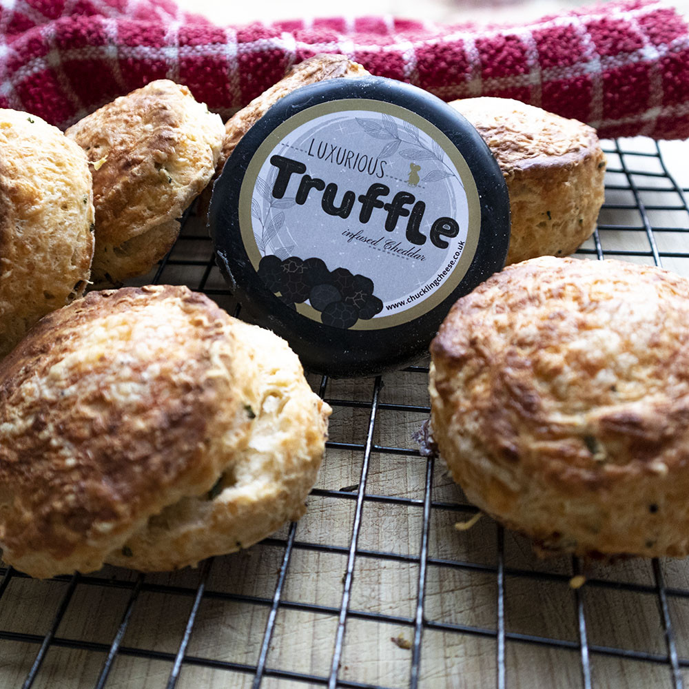 Golden cheese scones spread across a wire cooling tray with a red tea towel in the background. One cheese scone on the left has been opened, showing the heavy flecks of truffle and lashings o